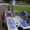 Le Velo-Plus est un cycle qui permet de transporter une personne en fauteuil roulant manuel sur une plate-forme.
